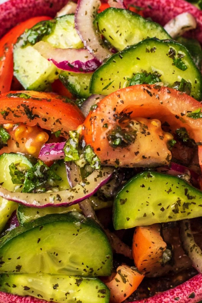 Sliced cucumbers, tomatoes and red onion coated in mint sauce