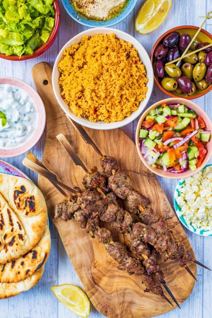 Greek Lamb Souvlaki skewers on a wooden board with cous cous, salad, olives and tzatziki