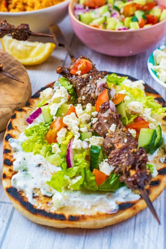 Greek Lamb skewer on a flatbread with tzatziki and salad