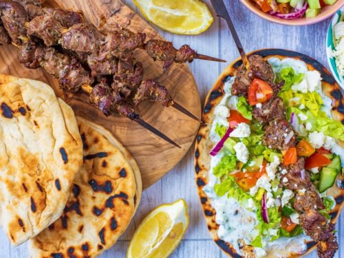 Greek Lamb Souvlaki skewers on a serving board next to flatbreads and lemon wedges