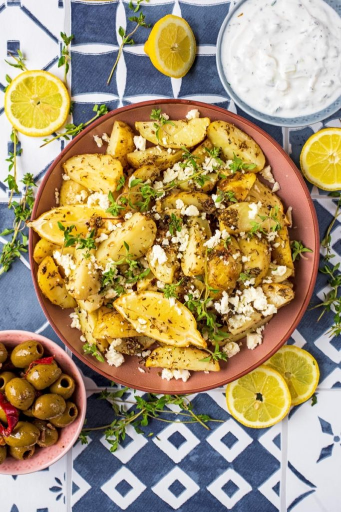 Greek Potatoes surrounded by tzatziki, olives and sliced lemons