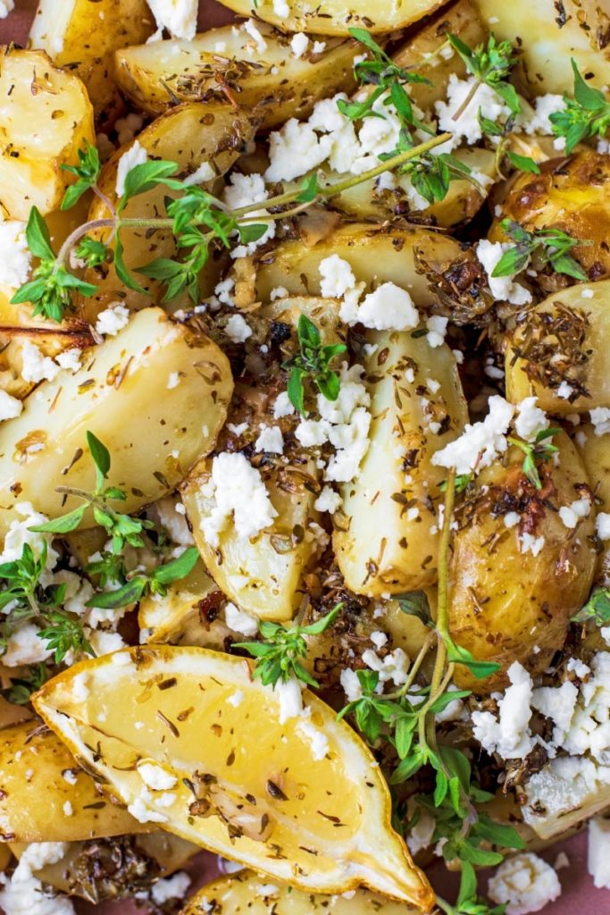 Cooked new potatoes covered in seasoning and sprinkled with feta