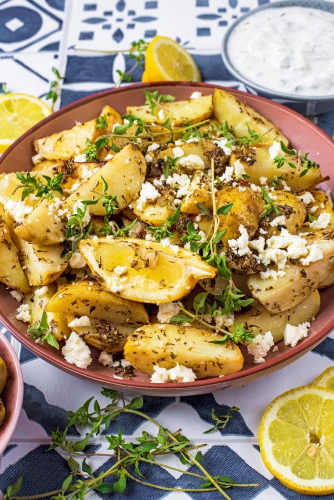 Greek Potatoes topped with lemon wedges, feta and sprigs of thyme
