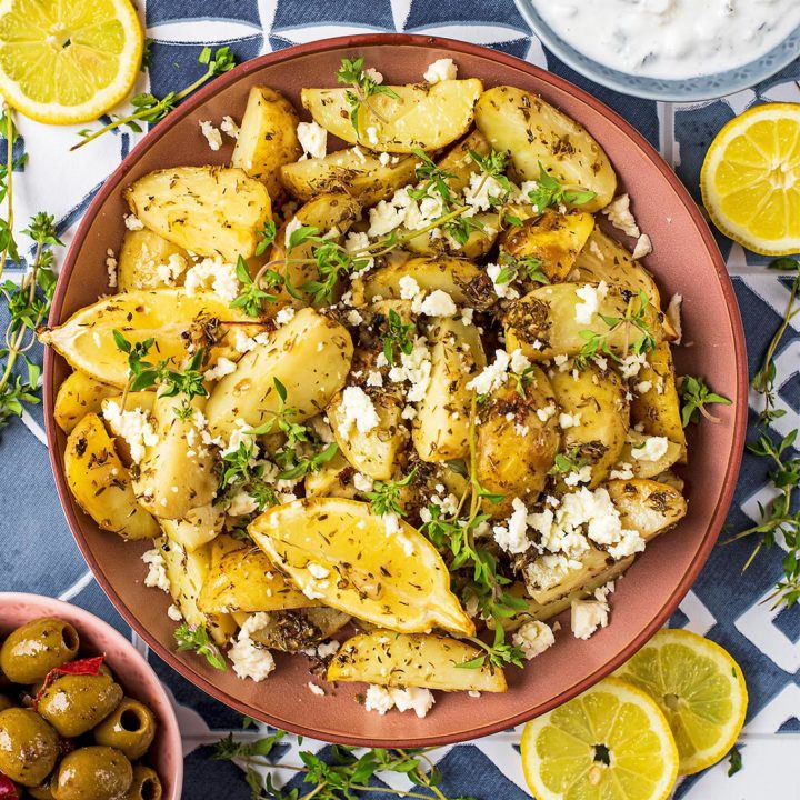 A large bowl of Greek Potatoes with lemon wedges and a small bowl of olives