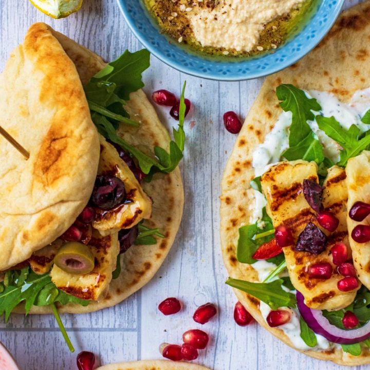 Grilled Halloumi Greek Flatbreads on a wooden surface with pomegranate seeds scattered around