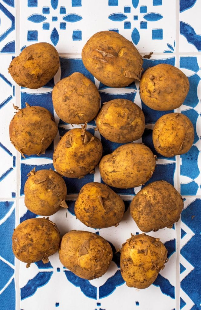 Dirty potatoes on a blue and white tiled surface