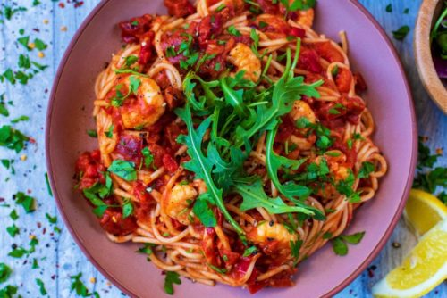 Prawn and Chorizo Pasta in a bowl with rocket lettuce leaves on top
