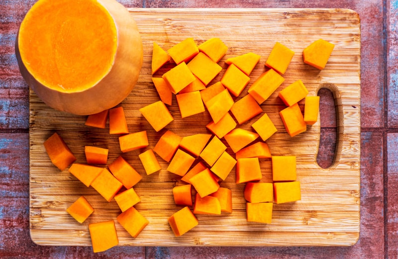 A chopping board with half a butternut squash and cubes of diced butternut squash