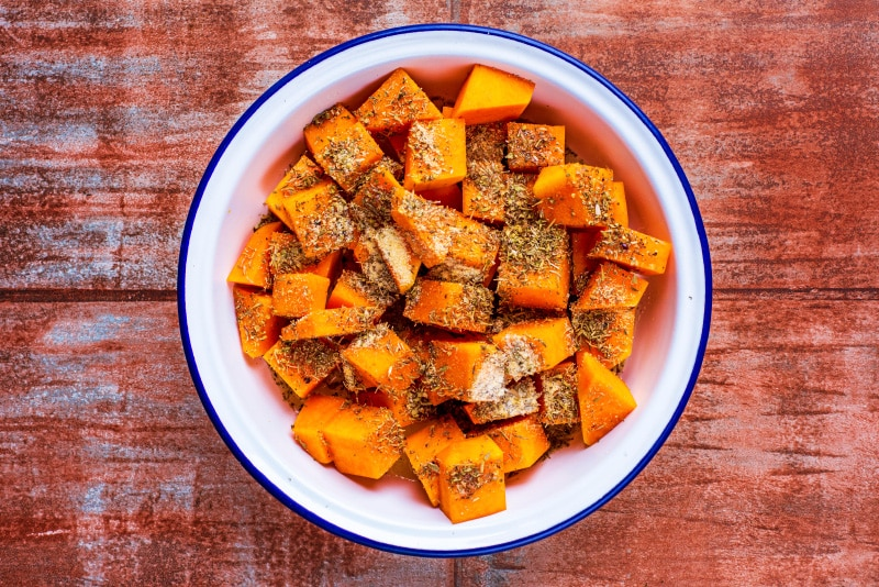 A white bowl containing seasoned cubes of butternut squash