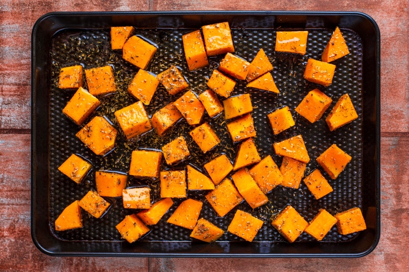 A black baking tray covered in cubes of raw butternut squash