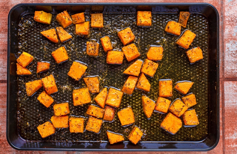A black baking tray covered in cubes of cooked butternut squash