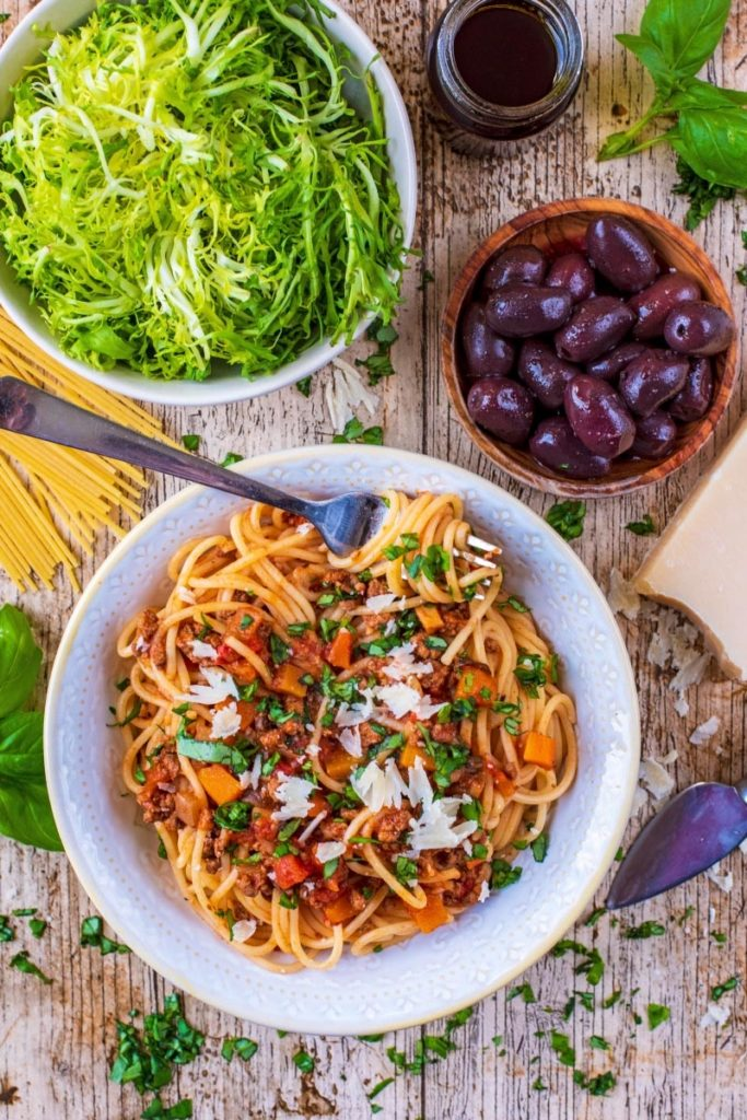 Slow Cooker Spaghetti Bolognese with a bowl of salad and some black olives