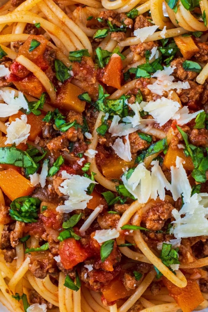 Slow Cooker Bolognese mixed with spaghetti, topped with basil and parmesan