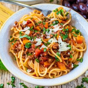 A white bowl of Slow Cooker Bolognese surrounded by various ingredients