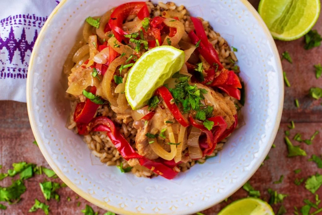 Slow Cooker Thai Chicken Curry in a white bowl, topped with a lime wedge