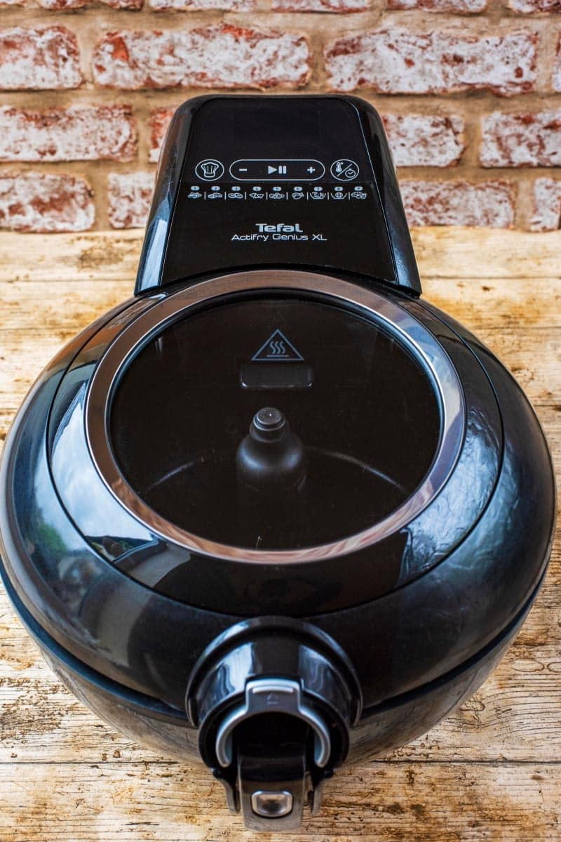 A black Tefal Actifry Genius in front of a brick wall