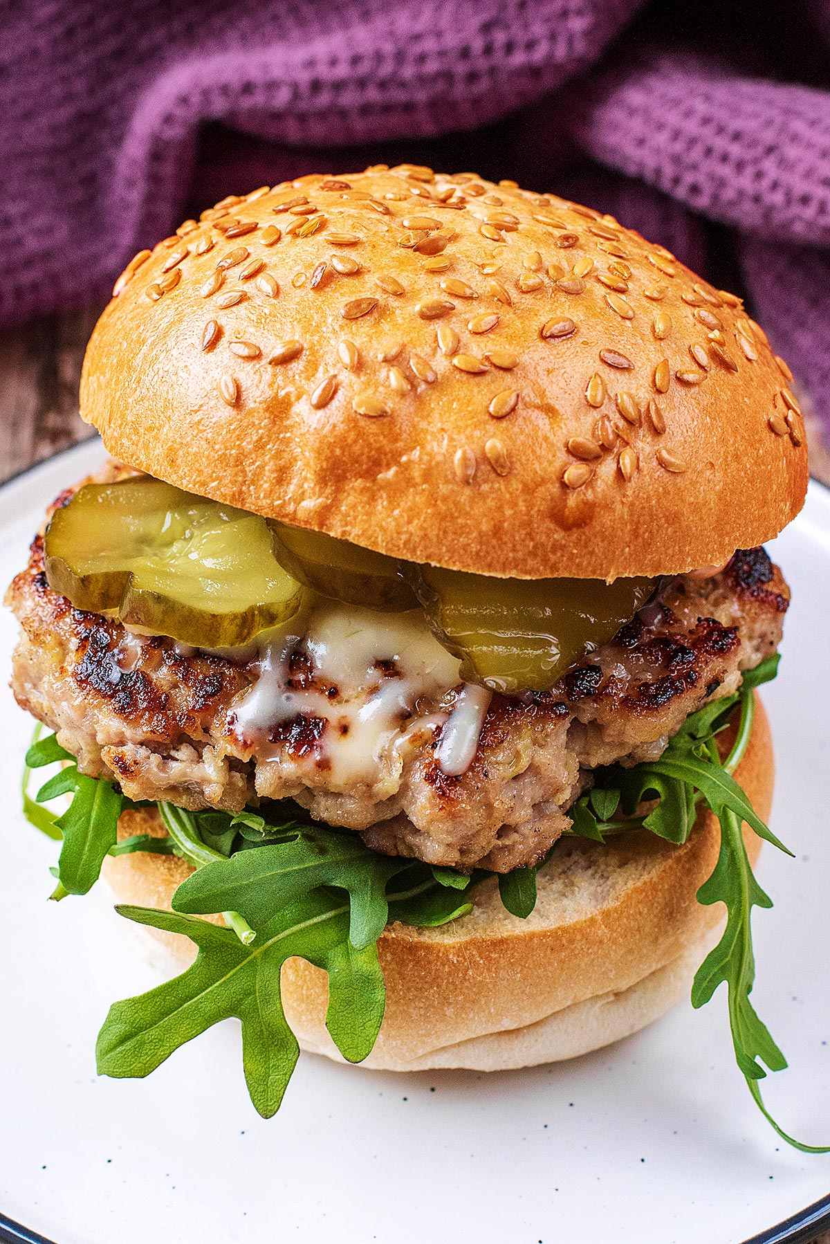 A burger in a sesame seed bun with lettuce leaves, pickles and melted cheese