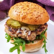 Pork and apple burger in a sesame seed bun with lettuce and pickles.