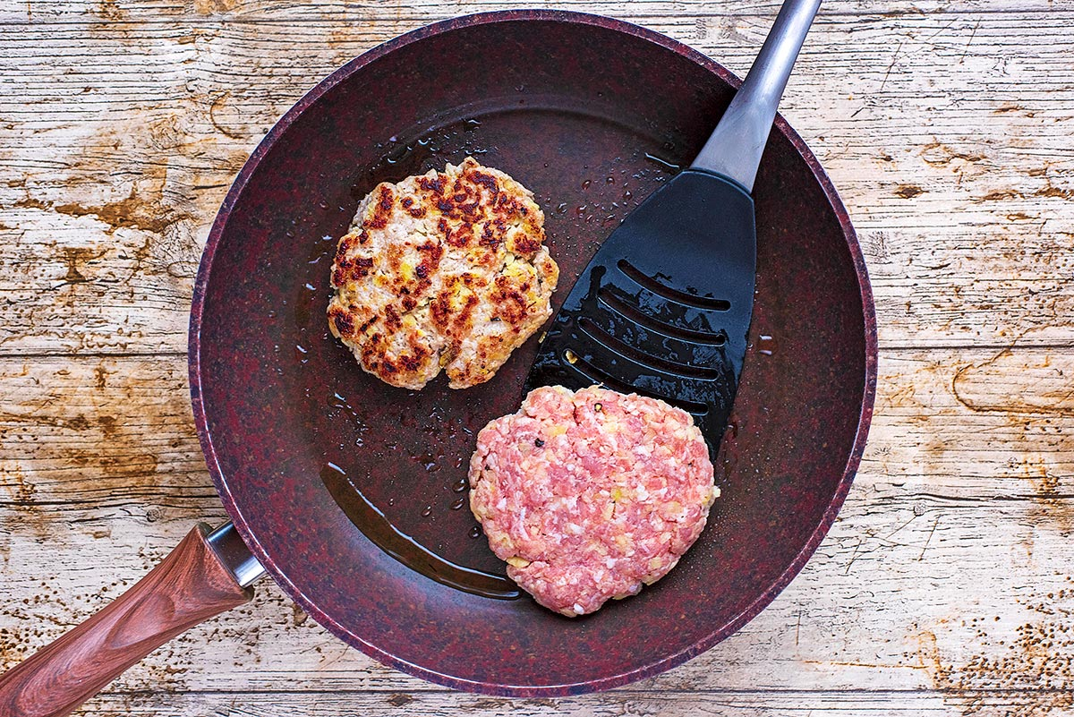 Two burgers cooking in a frying pan