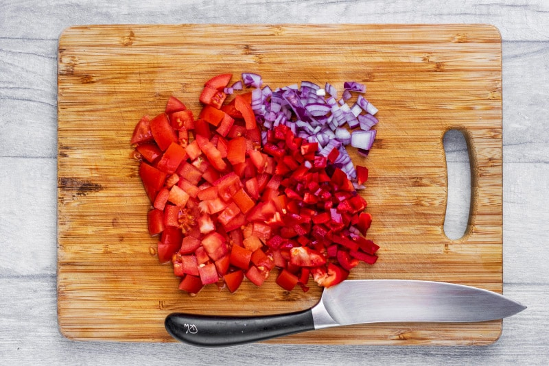 a wooden chopping board with chopped tomatoes, red pepper and onion