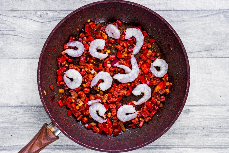 A frying pan with chopped red pepper, red onion, chopped chorizo and raw king prawns