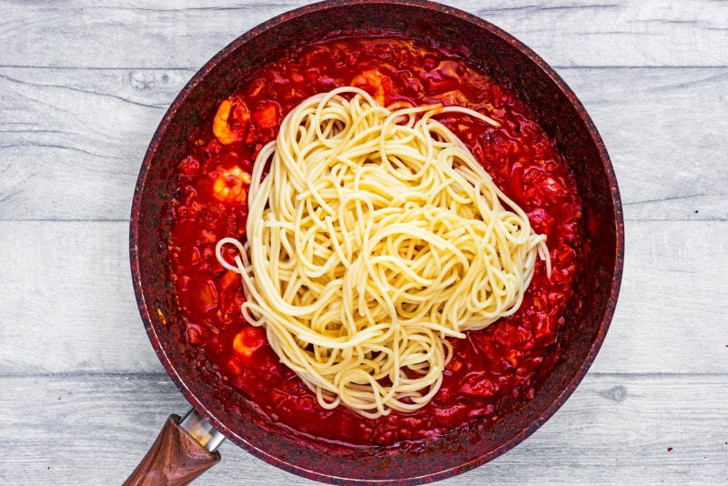 A frying pan with a prawn and chorizo tomato sauce and cooked spaghetti