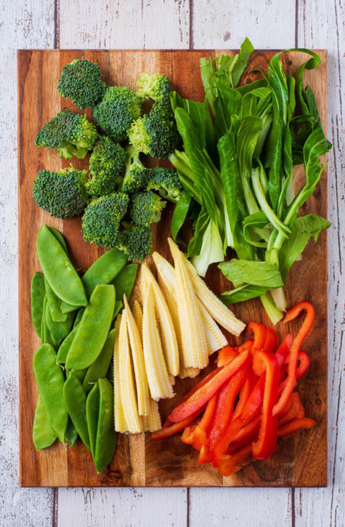 A chopping board with broccoli, pak choi, red pepper, baby corn and mangetout