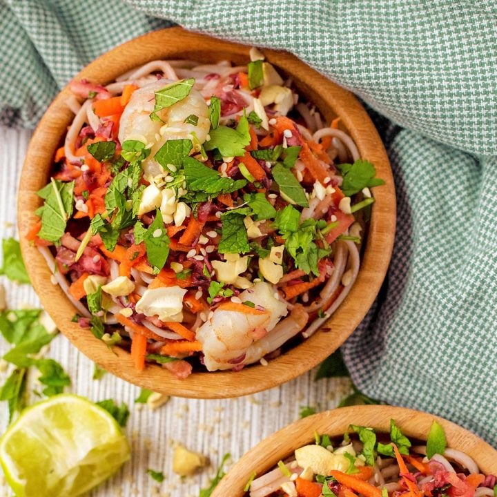 Garlic Prawn Noodles with chopped coriander on top. Sliced chillis are scattered around