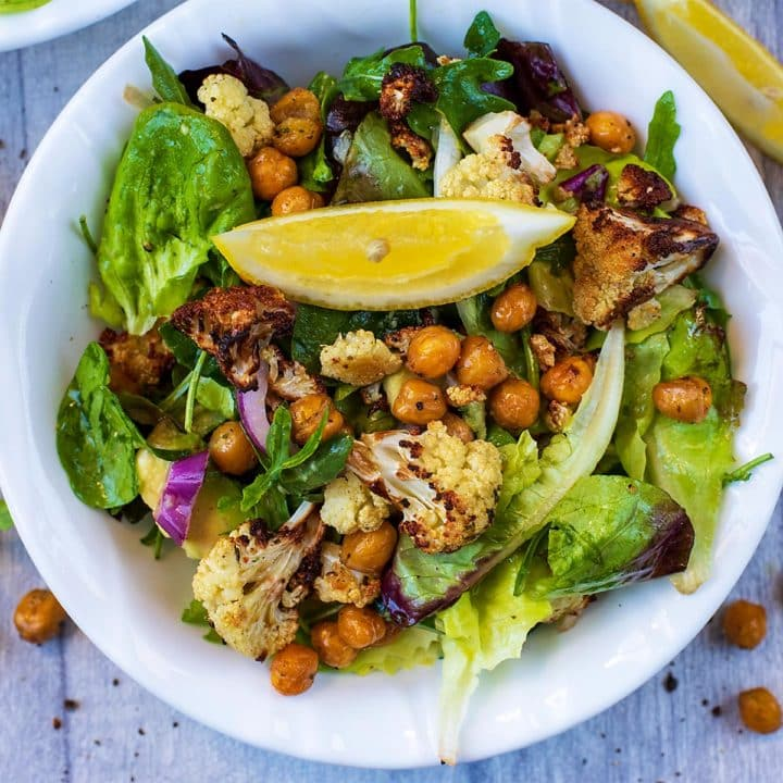 Roasted Cauliflower Salad in a white bowl, surrounded by lemon wedges and chickpeas