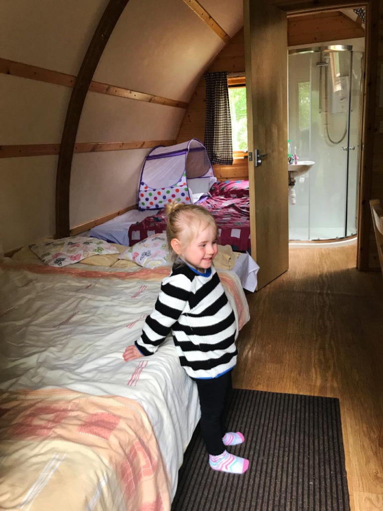 The inside of a wigwam showing both beds. A blond child stands next to one of the beds