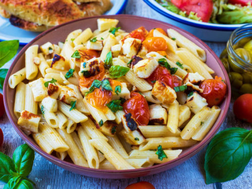 Halloumi pasta on a large pink plate, topped with tomatoes and herbs