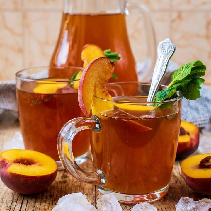 A glass of Peach Iced Tea with a spoon and mint leaves