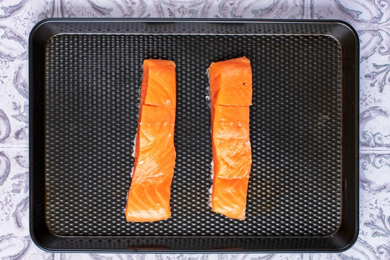 Two uncooked salmon fillets on a black baking tray