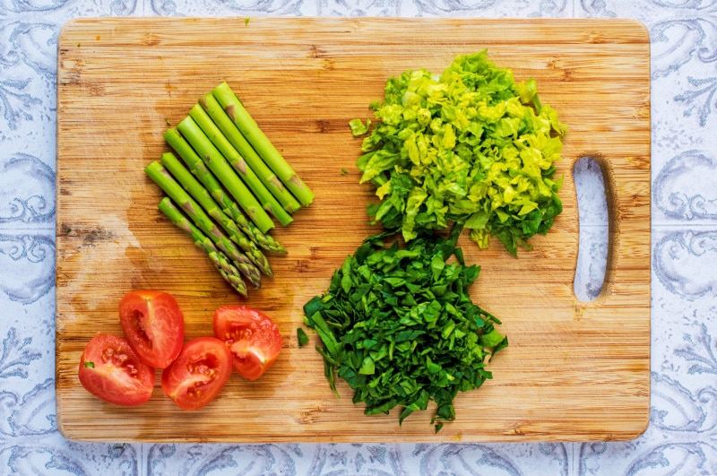 A wooden chopping board with chopped lettuce, asparagus and tomatoes