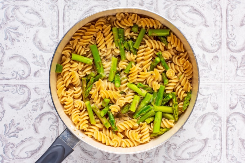 A saucepan containing cooked fusilli pasta and asparagus