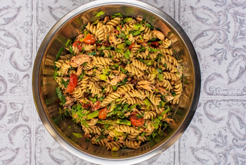 A large metal bowl containing a mixed salmon pasta salad