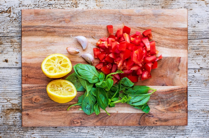 Chopped tomatoes, basil leaves, garlic cloves and two lemon halves on a wooden chopping board