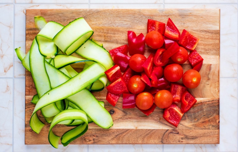 Sliced zucchini, chopped red bell pepper and cherry tomatoes on a wooden chopping board