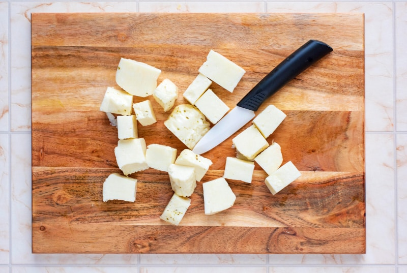 Halloumi cut into cubes on a wooden chopping board