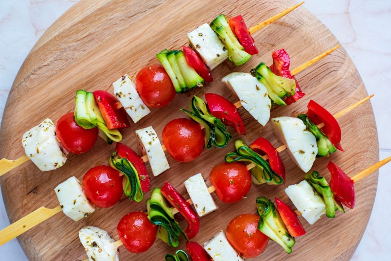 A circular wooden board with vegetable and halloumi skewers on it