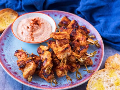 Paprika Chicken Skewers on a plate with paprika dip. Toasted slices of bread are next to the plate