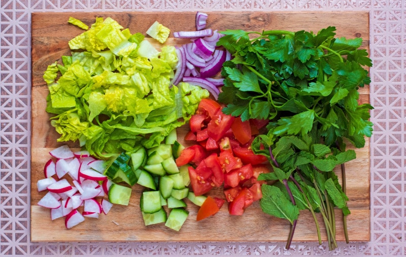 Chopped lettuce leaves, tomatoes, radish, cucumber and red onion on a wooden chopping board