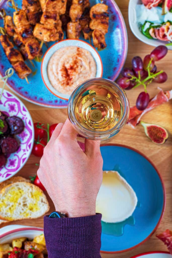 A hand holding a glass of white wine over a selection of tapas dishes