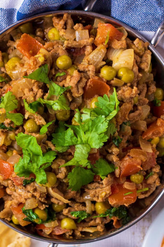 A dish of Lamb Keema containing minced lamb, peas, tomatoes, spices and cilantro