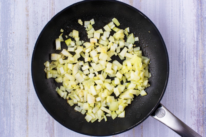 A black frying ban with chopped onions in it