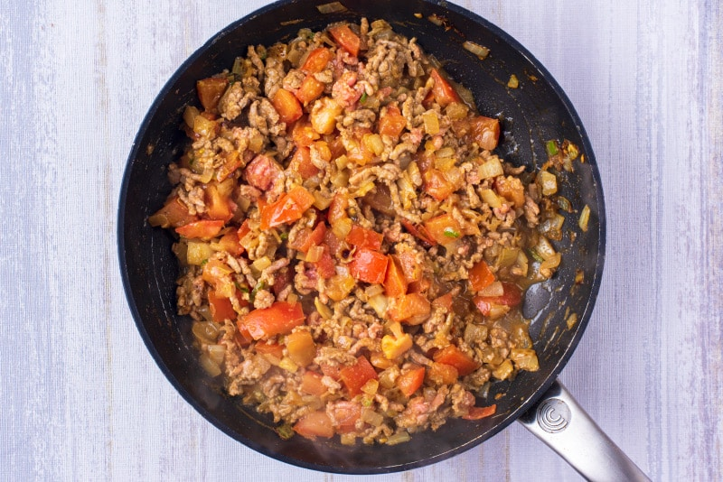 A black frying pan with chopped onions, green chili, grated ginger, spices, minced lamb and chopped tomatoes