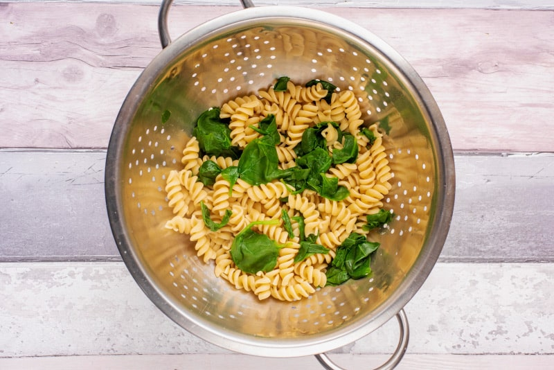 A colander containing drained cooked pasta and spinach