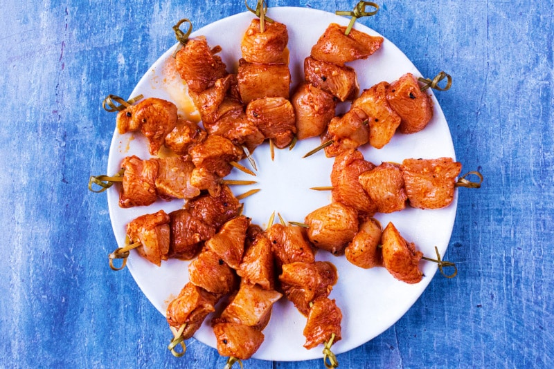 12 uncooked chicken skewers arranged in a circle on a white plate