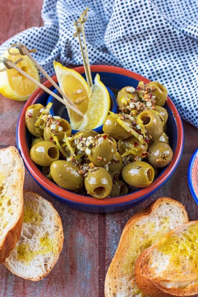 A blue and red bowl filled with green olives next to some toasted bread and a spotted towel