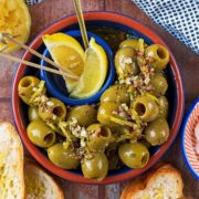 A bowl of green Spanish olives with lemon wedges, Bread and dip are next to it